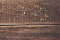 Paperclips variopinti sul fondo di legno d'annata della tavola immagine stock