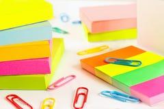 Paperclips y etiquetas engomadas multicoloras en el primer de escritorio blanco Fotos de archivo libres de regalías