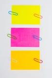 Paperclips y post-it coloridos en el fondo blanco aislado Fotografía de archivo