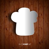 Papercut chef hat on wooden background Royalty Free Stock Image