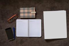 Papernote med mobilen, pennan och glasögon på mattan Royaltyfria Bilder