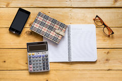 Papernote with mobile, eyeglasses and calculator on the wood tab Royalty Free Stock Image