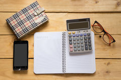 Papernote with mobile, pen, eyeglasses and calculator on the woo Royalty Free Stock Images