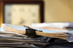 Papers. Pile of papers on a table and clock Stock Photos