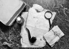 Papers and book on detective work table with tools. Retro papers and book on detective work table with tools background Stock Photos