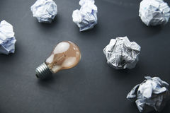 Papers and  bulb. Crumpled office paper and light bulb Royalty Free Stock Photos
