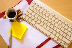 Papers on a desk with cup of coffee royalty free stock photo
