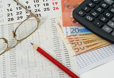 Papers with figures, calendar, glasses, red pencil, euros Royalty Free Stock Images