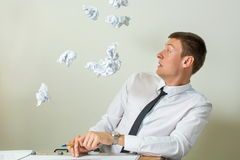 Papers flying into young businessman face Stock Photos