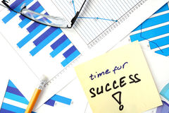 Papers with graphs and words time for success. Royalty Free Stock Photo
