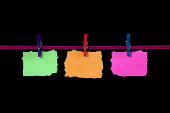 Papers on a line. Three bright coloured pieces of paper hanged to a ribbon line with washing pegs on a black background royalty free stock photos