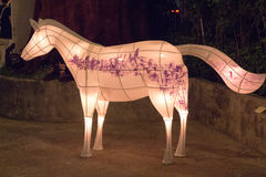 Papers mache horse with warm ight and purple decoration symbolizing freedom and escape from modern life in an art park. Paper mache horse with warm ight and Royalty Free Stock Images