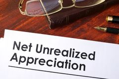 Papers with Net unrealized appreciation NUA. Papers with Net unrealized appreciation NUA on a table Stock Image