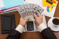 Papers on the office table, financial report, cash in hand. Folders with papers on the office table, financial report, cash in hand Stock Image