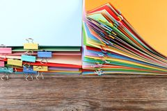 Papers with paperclips and clamps. Stack of colored papers with paperclips and clamps on wooden table stock photography