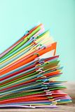Papers with paperclips. Stack of colored papers with paperclips on wooden table Stock Photography