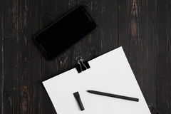 Papers with pen and cellular on wooden background Royalty Free Stock Image