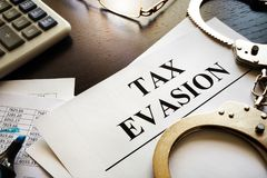 Papers about tax evasion on a desk. Tax avoidance concept stock image