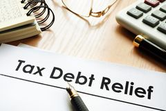 Papers with title tax debt relief. Papers with title tax debt relief on a desk royalty free stock photos