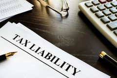 Papers with title tax liability on a desk. Taxation concept Royalty Free Stock Photo