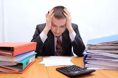 Paperwork. Businessman is stressed with large paperwork and has headache Royalty Free Stock Images