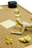 Paperwork. Cork noticeboard with sticky post-it notes, pins and a wooden model dummy doll - office paper work - office paperwork Stock Image