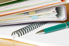 Paperwork. Some folders, a notebook and a pen on a desk. Focus on the tip of the pen Royalty Free Stock Photo