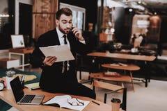 paperwork biznesowego mężczyzna s kostium patrzeje Opowiadać na telefonie zdjęcie royalty free