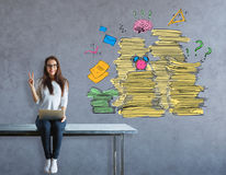 Paperwork concept. Cheerful young european girl sitting on table and showing peace sign on concrete background with paperwork piles. Workload concept Stock Photo