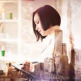 Paperwork concept. Side view of woman writing in notepad on abstract city background. Paperwork concept. Double exposure Stock Photography
