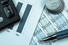 Paperwork, money management, calculating income and expenses. Close up of financial grahs with calculator,pen and silver money coins Royalty Free Stock Photo