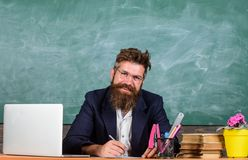 Paperwork part of teachers life. School teacher checking homework or test. Teacher sit desk with laptop. Check homework. Teacher bearded hipster with royalty free stock photos
