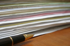 Paperwork (side view). Stack of paper and a pen besides it, focus on pen's tip stock images