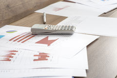 Paperwork with statistical data, graphs and charts lying on a wo. Oden office desk together with a pen and calculator Royalty Free Stock Photography