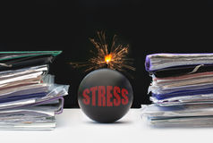 Paperwork stress. Exploding bomb inbetween two stacks of paperwork Stock Images