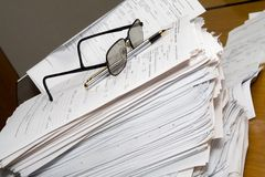 Paperwork-working late concept. Lots of paperwork ahead - concept for working late and short deadlines royalty free stock image
