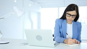 Paperwork, Young Businesswoman Writing and Working on Laptop royalty free stock photo