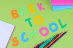 Papeterie et inscription multicolore de nouveau au schooll sur un fond vert image stock