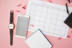 Papeterie, vie immobile avec le calendrier et les accessoires, carnet vide, horloge et smartphone photos stock