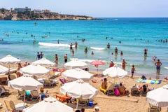 PAPHOS, CHIPRE - 24 DE JULHO DE 2016: Turistas e locals que apreciam um dia de verão agradável em Coral Bay Beach Foto de Stock Royalty Free