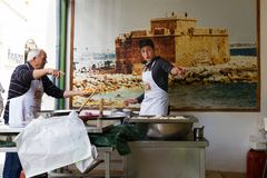 Man and boy cooking traditional Cypriot loukoumades pastry and s royalty free stock photography