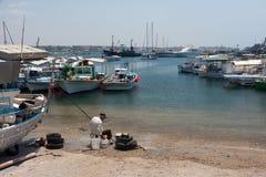 PAPHOS, CYPRUS/GREECE - 22 JULI: Oude mens die voorbereidingen treffen te vissen van stock foto's