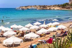 PAPHOS, CYPRUS - JULY 24, 2016: Tourists, sunbeds and umbrellas on hot summer day at Coral Bay Beach Royalty Free Stock Images
