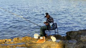 Paphos, Cyprus - September 17, 2017 - Fisherman with fishing rod. Fisherman sits on the chair near the river with fishing rod. Elderly man cathes fishes from stock footage