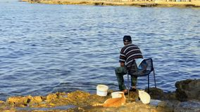 Paphos, Cyprus - September 17, 2017 - Fisherman relax with fishing rod near sea. Fisherman sits on the chair near the river with fishing rod. Elderly man cathes stock video