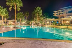 Paphos, Cyprus - September 19, 2016: Night view of the hotel`s pool, palm trees, sun beds and a cafe. royalty free stock photography