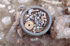 Археологические раскопки Человеческие косточки остатков скелета в земле и немногом нашли в артефактах усыпальницы в разбивочном b стоковые изображения rf