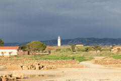Paphos Lighthouse. View of  lighthouse from the archeological site of Paphos.The lighthouse on the hill, harbour, landscape, cloudy sky Royalty Free Stock Images
