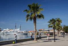 Paphos seafront with palm trees , fisherman and boats on April 20 in Paphos, Cyprus.Paphos -ancient city included in UNESCO list Royalty Free Stock Photography