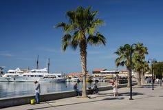 Paphos sjösida med palmträd, fiskaren och fartyg på April 20 i Paphos, Cypern Paphos - forntida stad som är inklusive i UNESCOlis Royaltyfri Fotografi